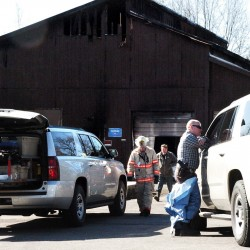 Jeremy Damren, right, speaks with another investigator from the state fire marshal's office Wednesday while determining the cause of a fire that destroyed a barn housing a licensed medical marijuana growing operation Tuesday. Behind Damren are Fairfield Fire Chief Duane Bickford, left, and property owner Doug Dixon.