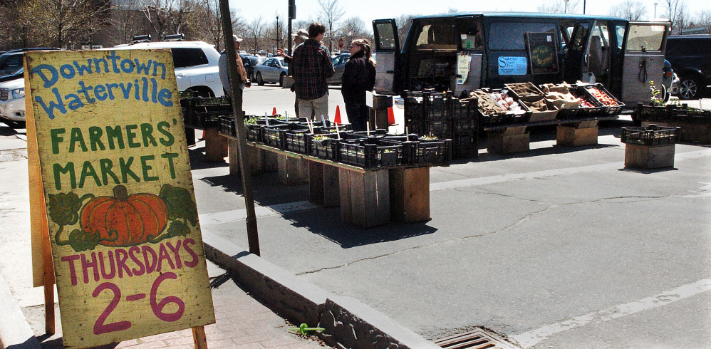 Shoppers speak with farmers from Snakeroot Organic Farm on Thursday, the first day of the seasonal Downtown Waterville Farmer's Market at The Concourse in Waterville.