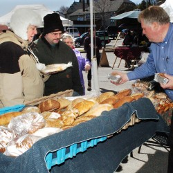 Karl Rau, of Good Bread, sets out his products as customers Jeannie and David Gubbins Jr. wait to buy bread Thursday at the Downtown Waterville Farmer's Market. The market opened for the season and will be in The Concourse parking lot every Thursday through Nov. 17.