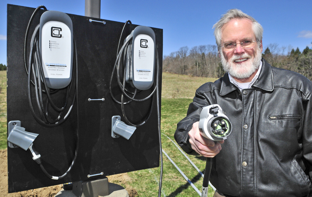 Scott Cowger holds up an electric car charging plug Thursday at the Maple Hill Farm Inn and Conference Center in Hallowell.