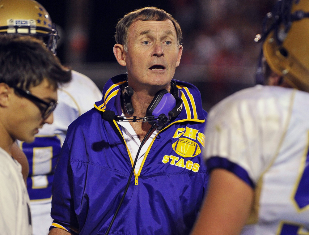 John Wolfgram speaks with Cheverus football players during a 2010 game. On Monday, Wolfgram announced his retirement after four decades of coaching.(Staff file photo by Gordon Chibroski)