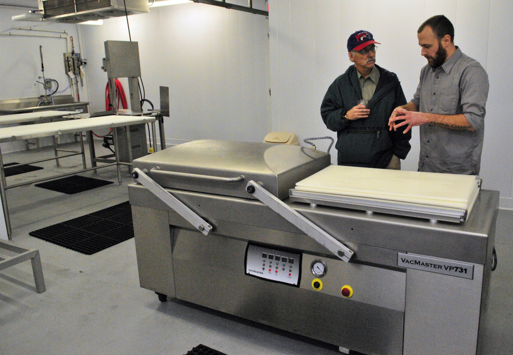 City councilor Phil Hart, left, talks about a cryovac packaging machine with Eben Harrington, the hazard analysis and critical control points manager, during a tour of the Central Maine Meats processing facility in Gardiner.