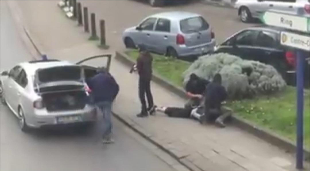 In this image made from video, police arrest a man in the Anderlecht area of Brussels on Friday.