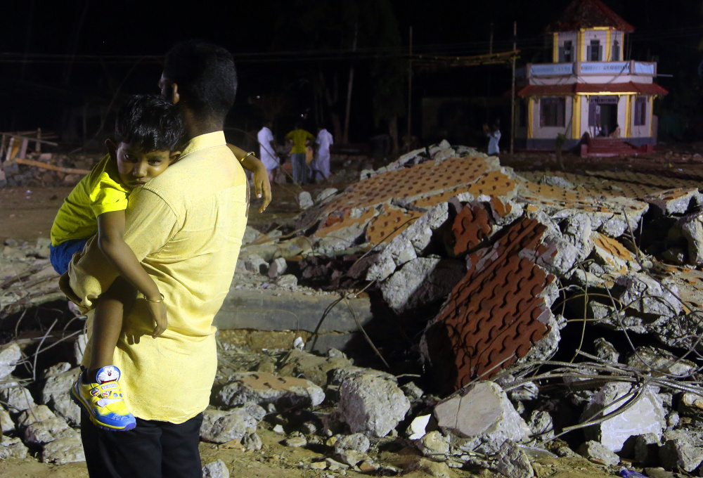 A man carries his child past the debris of a damaged building where a massive fire broke out during a fireworks display at the Puttingal temple complex in Paravoor, India.