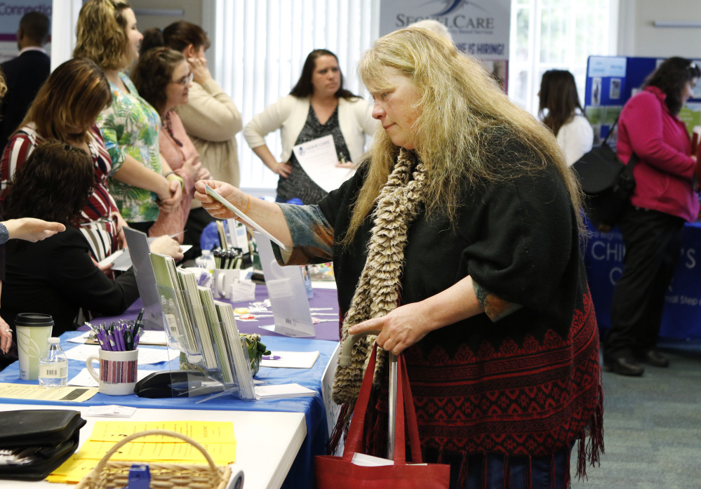"""Lois Dersham, who lost her job when Merrymeeting Behavioral Health Services closed, checks out employers Monday at a job fair in Brunswick. """"I'd like to find a similar job, but now I worry a little about the field I'm in,"""" she said."""