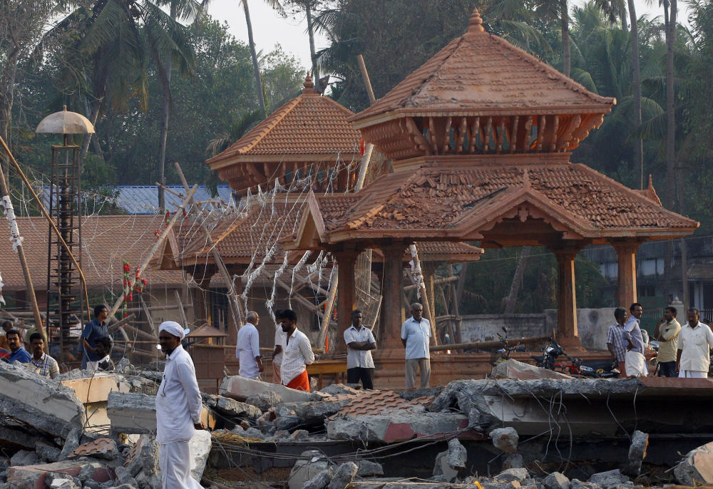 People check out the damaged structures after a massive fire broke out Sunday during a fireworks display at the Puttingal temple complex in Paravoor village, Kollam district, southern Kerala state, India, Monday.