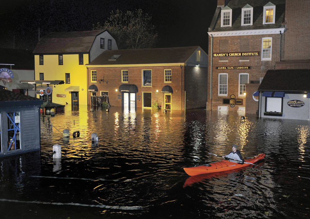 A kayaker paddles through waters flooding Bowen's Wharf after Superstorm Sandy in historic Newport, R.I.