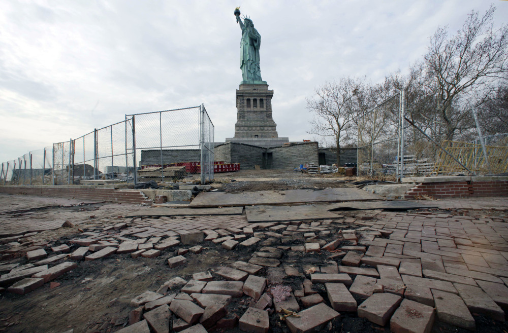 The Statue of Liberty stands beyond parts of a brick walkway damaged in Superstorm Sandy on Liberty Island in New York.