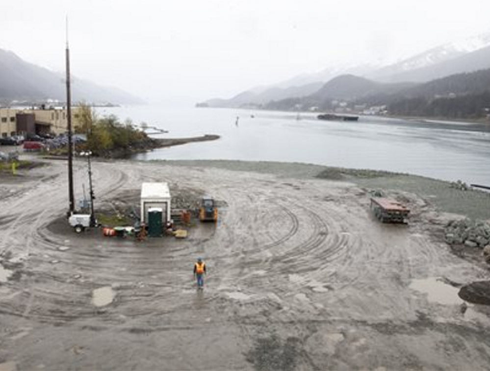A worker walks on the site that will soon host a life-sized whale sculpture and bridge park along a channel in Juneau, Alaska, a project that led a cruise ship group to sue the city.