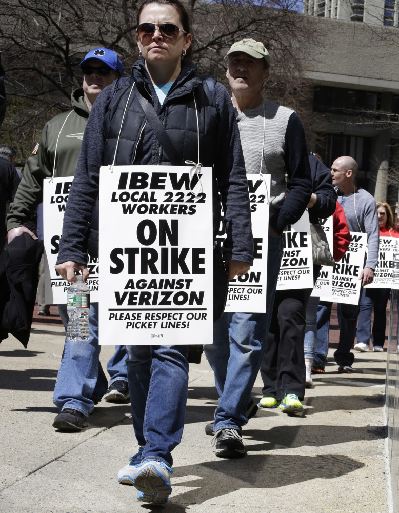 Verizon workers in Boston picket Wednesday. Tens of thousands walked off the job in several states.