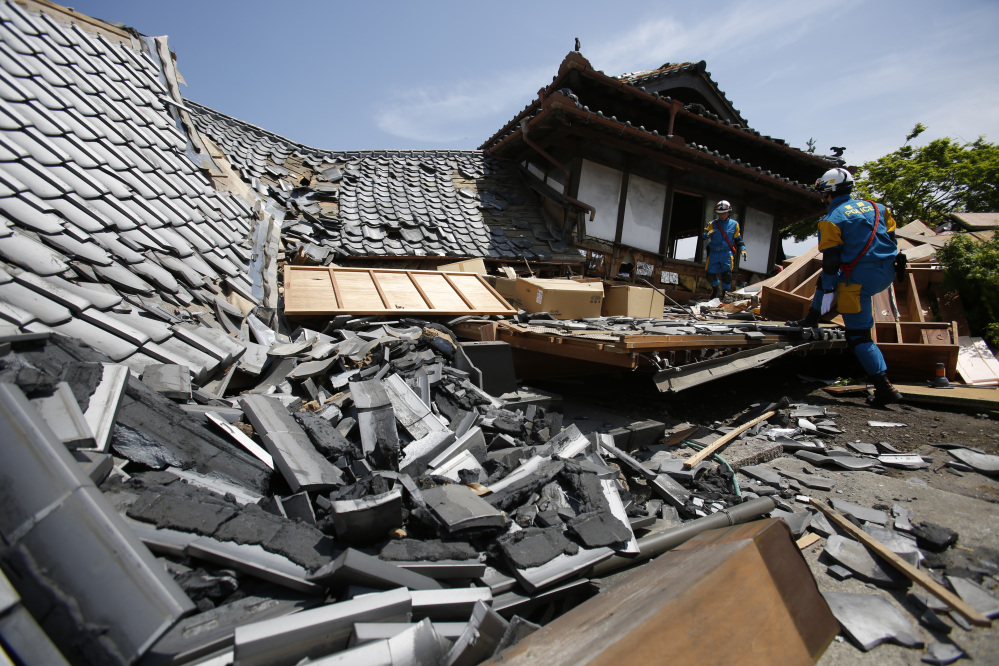 Police rescue team members search through damaged houses to check for trapped people in Mashiki, Kumamoto prefecture, southern Japan, on Friday, prior to the second earthquake striking.