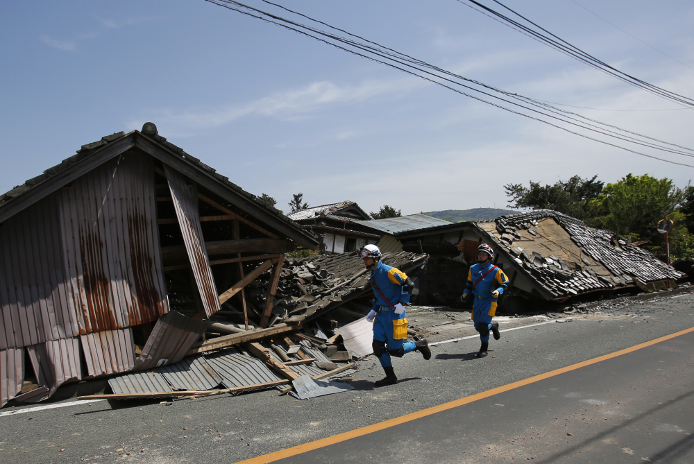 Police officers run in front of collapsed houses in Mashiki, Kumamoto prefecture, southern Japan, on Friday after the first earthquake struck.