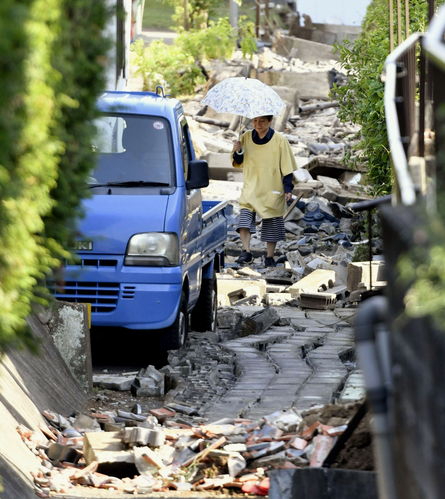 A resident walks through the debris after a magnitude-6.5 earthquake in Mashiki, Kumamoto prefecture, southern Japan, Friday.