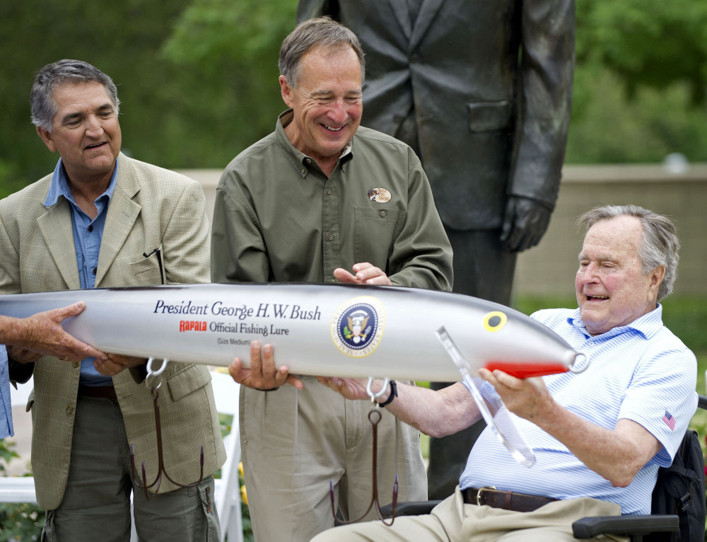 Bass Pro Shops founder Johnny Morris, center, joins Pedro Sors, president of the fishing association of the Mexican state of Tamaulipas, to present former President George H.W. Bush with a giant fishing lure Thursday at the Bush Library in College Station, Texas.