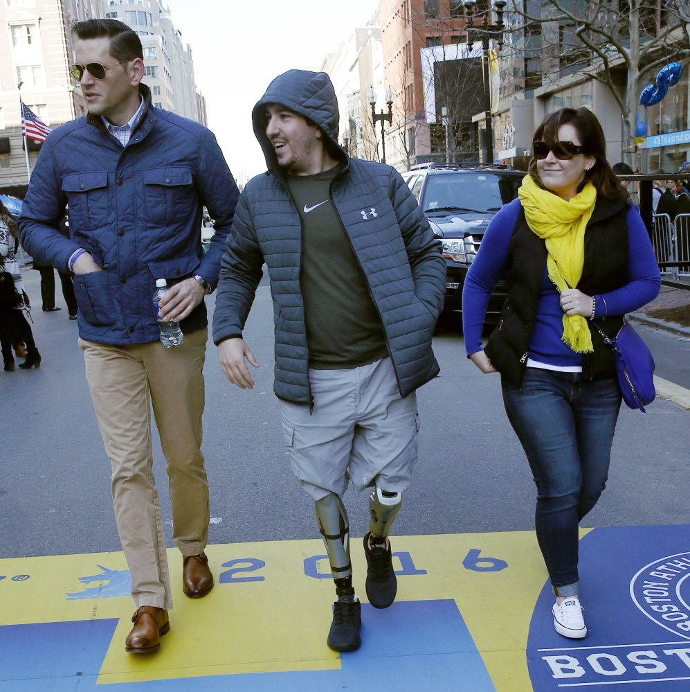 Boston Marathon bombing survivor Jeff Bauman, center, walks across the race's finish line Friday. He was among more than 260 injured in the 2013 bombings.