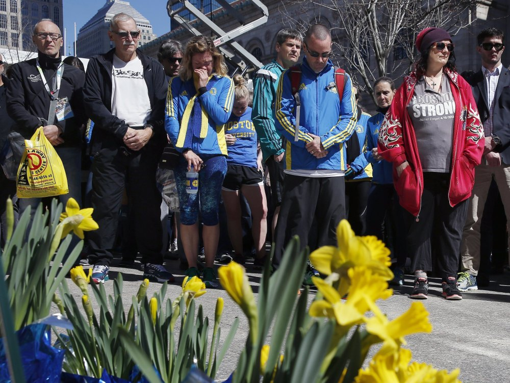 People observe a moment of silence Friday at the site where the first of two bombs detonated in 2013 at the Boston Marathon finish line on Boylston Street in Boston. Friday marked the third anniversary of the bombings, in which three died.