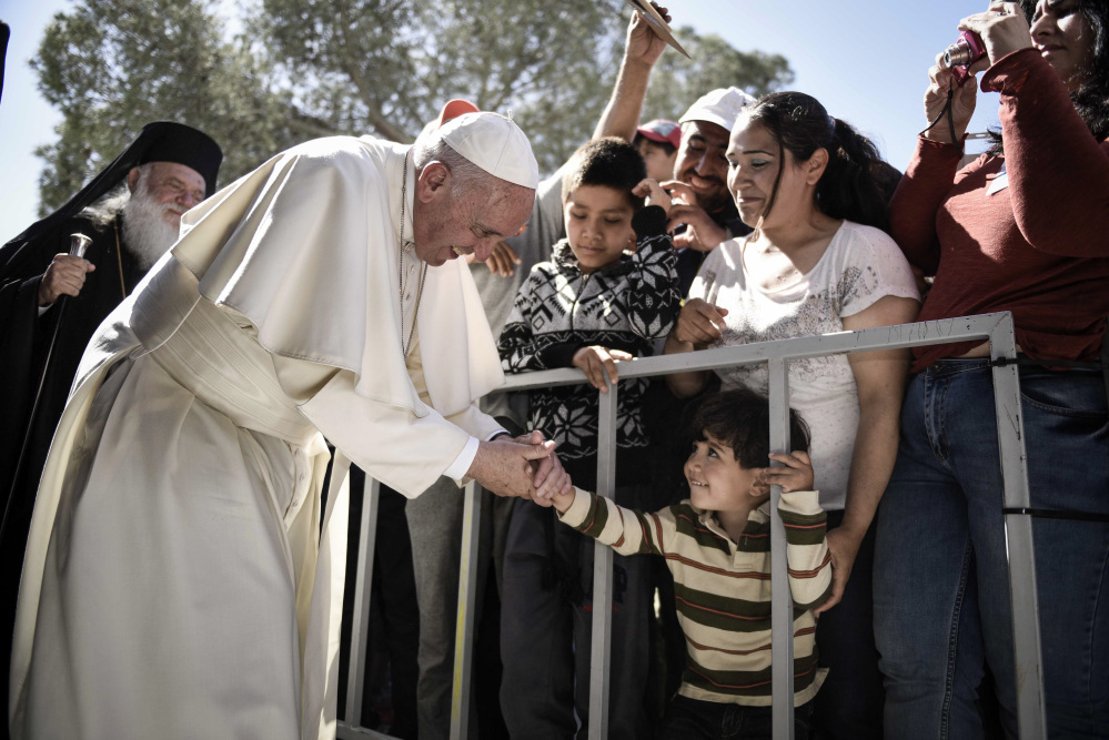 A child greets Pope Francis during a visit at the Moria refugee camp on the island of Lesbos, Greece.
