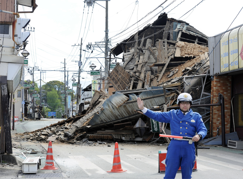 A police officer stands guard in front of a house destroyed by an earthquake in Mashiki, Kumamoto prefecture, southern Japan Saturday.