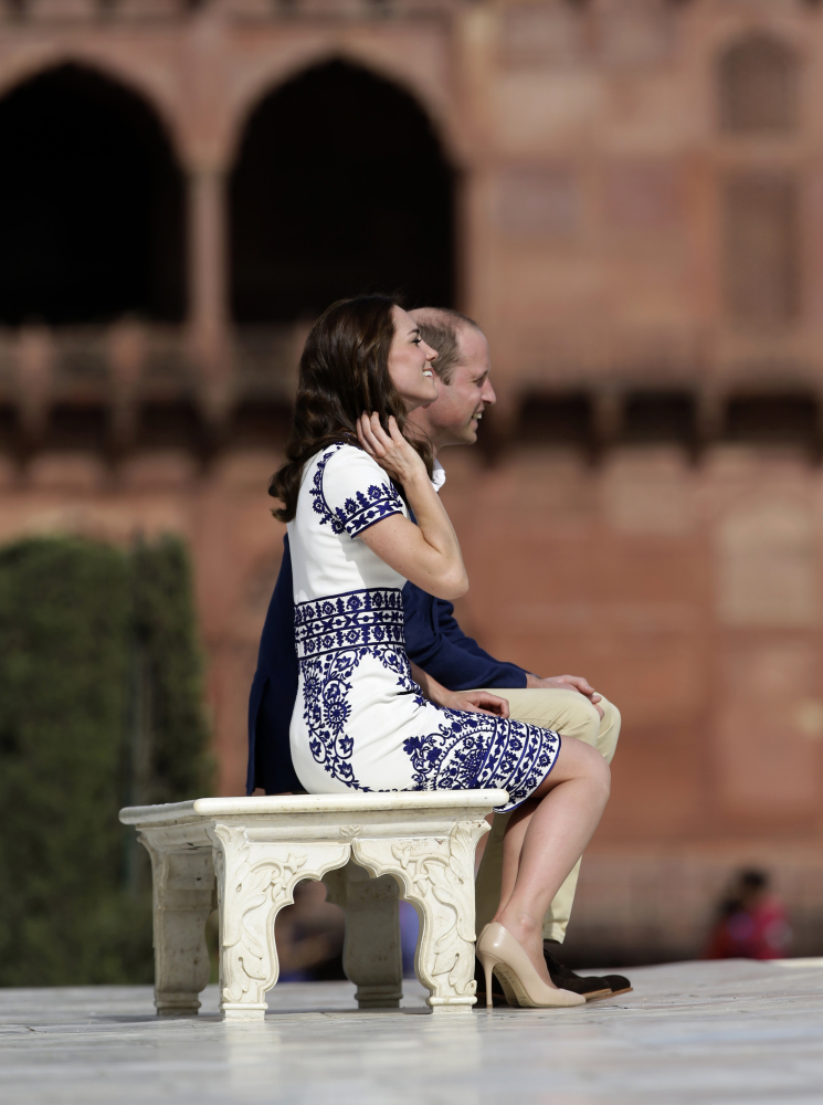 Britain's Prince William, along with his wife, Kate, the Duchess of Cambridge, pose for photographers on the same bench where the prince's mother, Princess Diana, famously posed in front of the Taj Mahal in Agra, India, on Saturday.
