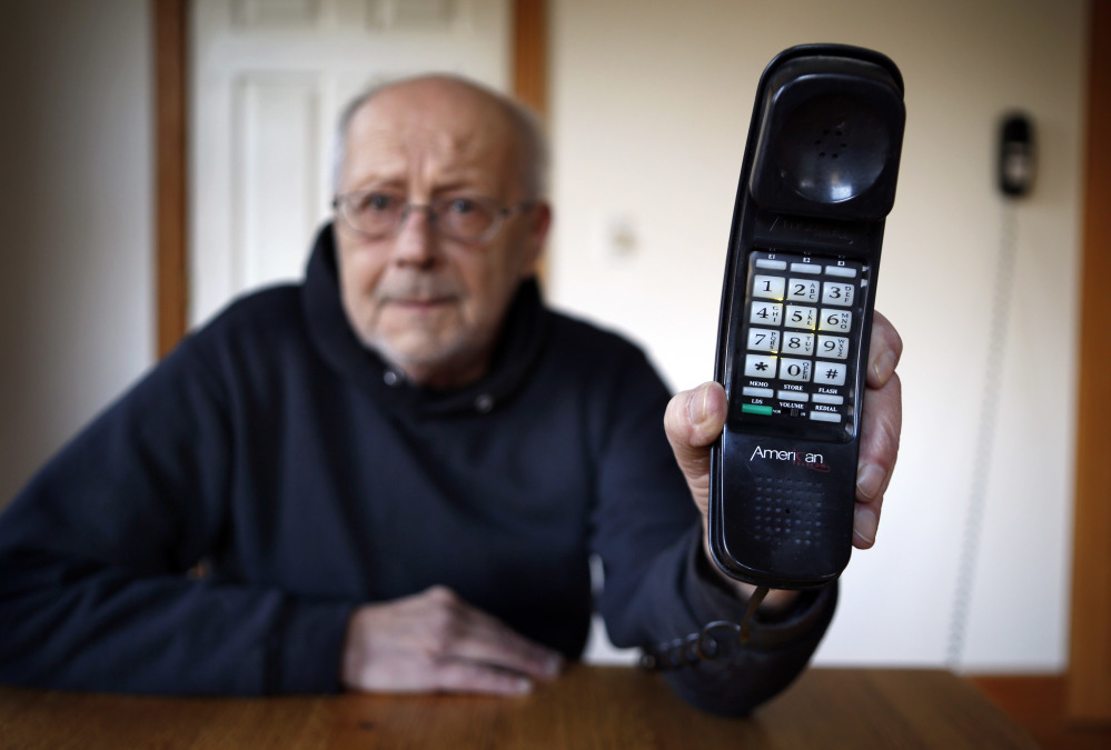 Peter Froehlich holds the landline telephone he uses at his rural home in Whitefield.. Across the country, telecom companies are lobbying lawmakers to be released from their mandate of providing service to every home.
