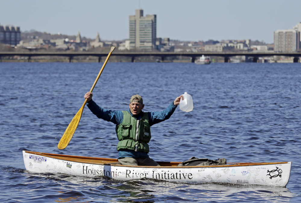 Denny Alsop, 69, of Stockbridge, Mass., celebrates on the Charles River as he finishes his monthlong paddle on Wednesday to highlight the need for clean water. He also drew attention to General Electric's resistance to the EPA's proposed Housatonic River cleanup.