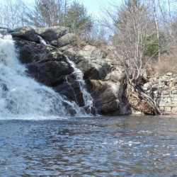 A waterfall at the western end of the reservoir and a rock wall from an old sawmill are highlights of a paddle in the Saco River Reservoir.