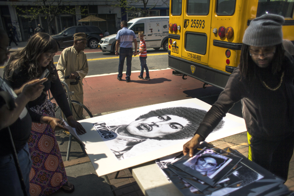 People buy posters and pictures of Prince outside of the Apollo Theater in New York on Friday.