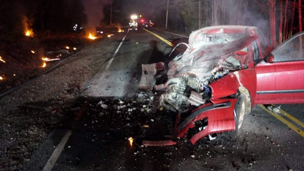 The wreckage of a Hyundai sedan sits in the middle of Route 118 in Norway. The car's driver, Jennifer Clough, 42, of Norway, was injured when another vehicle struck her car head-on late Friday and it burst into flames. Photo courtesy WSCH-TV 6.