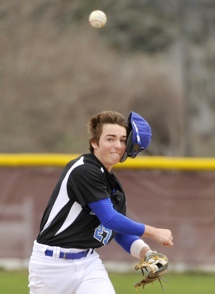 Kennebunk second baseman Derek Smith loses his cap while making a throw to first base for an out.