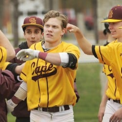 Cape Elizabeth's Dylan Roberts is greeted at home plate by his teammates after hitting a home run in the sixth inning Saturday against Kennebunk. The Capers won their season opener, 6-1.
