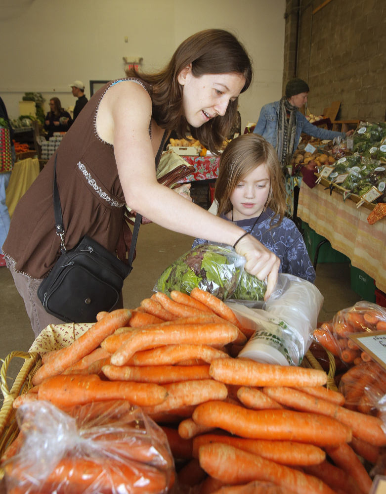 Jennifer Lehto buys carrots with her daughter Lexi Wilson-Lehto at the Portland Farmers Market on Saturday.