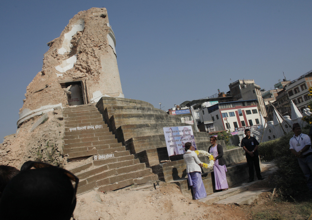 Volunteers hold a wreath as they await the arrival of Nepal's Prime Minister Khadga Prasad Oli, at the ruins of the iconic Dharahara tower in the Nepalese capital of Kathmandu on Sunday. A devastating earthquake hit Nepal one year ago.