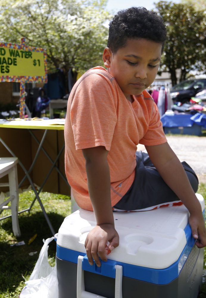 Nine-year-old Tristan Jacobson sits on a water cooler in front of his lemonade stand at his home in Springfield, Mo.