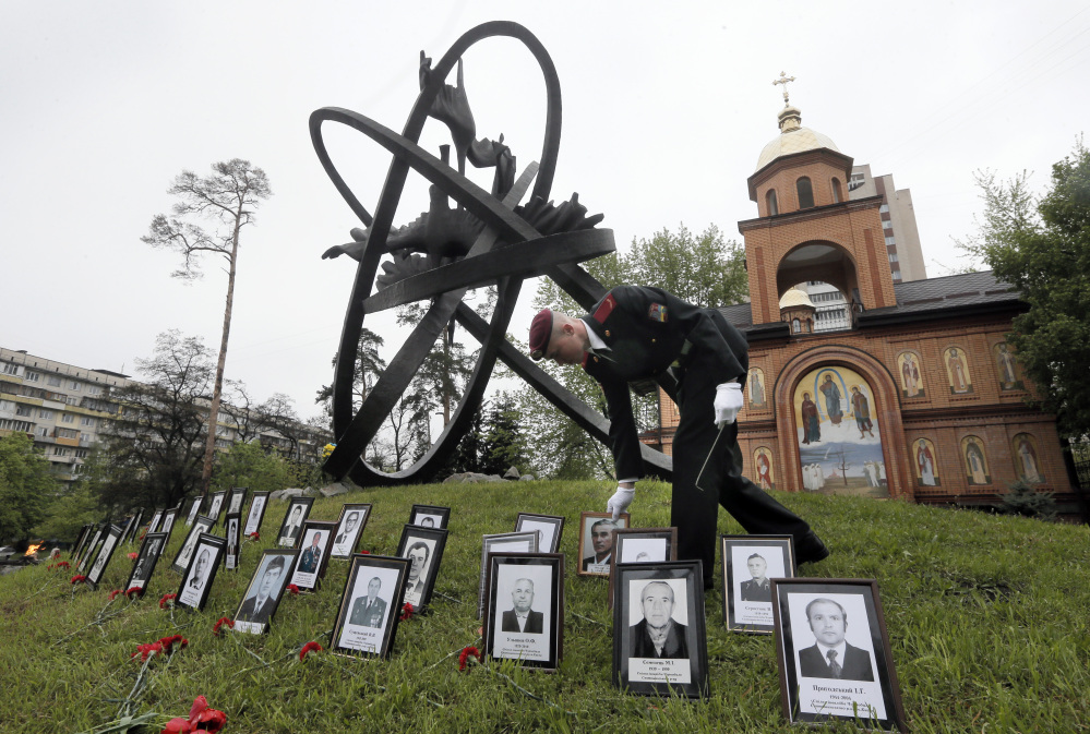 A soldier places portrait photos near the monument erected in memory of the victims of the Chernobyl explosion in Ukraine's capital Kiev, Ukraine, Tuesday.