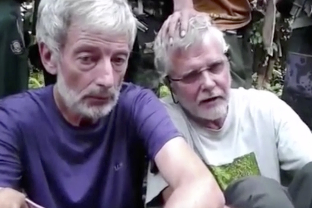 This image made from undated militant video, shows Canadians John Ridsdel, right, and Robert Hall.
