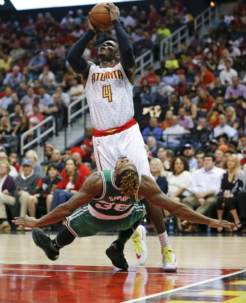 Atlanta's Paul Millsap knocks over Boston's Marcus Smart as he shoots during the Hawks' Game 2 win Tuesday night.   The Associated Press