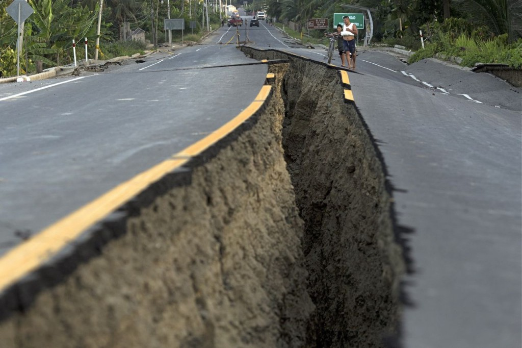 Residents look at a rift created by Saturday's  deadly 7.8-magnitude earthquake, in Chacras, Ecuador, Tuesday. The Associated Press