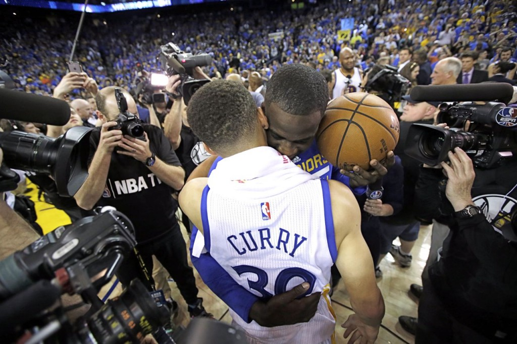 Golden State Warriors' Stephen Curry is hugged by teammate Draymond Green after the team's record-breaking 125-104 win over the Memphis Grizzlies Wednesday. The Associated Press