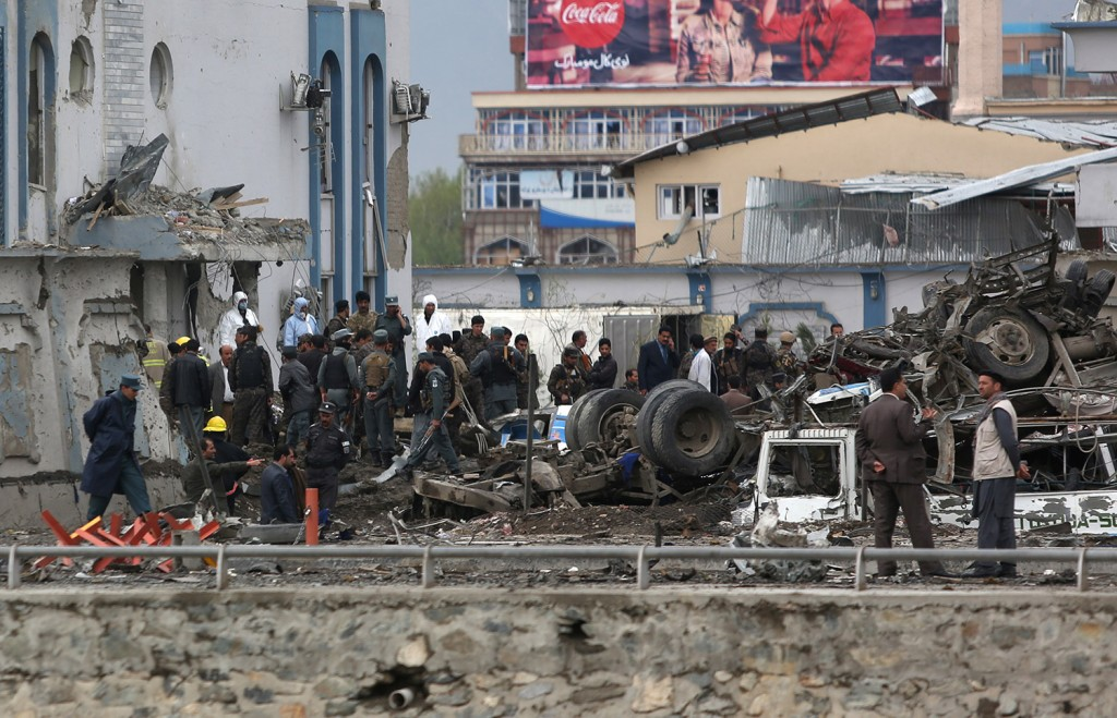 Afghan security forces inspect the site of a Taliban-claimed deadly suicide attack in Kabul. More than 300 people were injured.