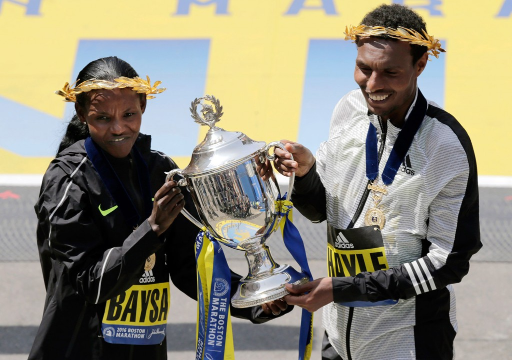 Atsede Baysa, left, and Lemi Berhanu Hayle, both of Ethiopia, hold a trophy after they won the women's and men's divisions of the 120th Boston Marathon.