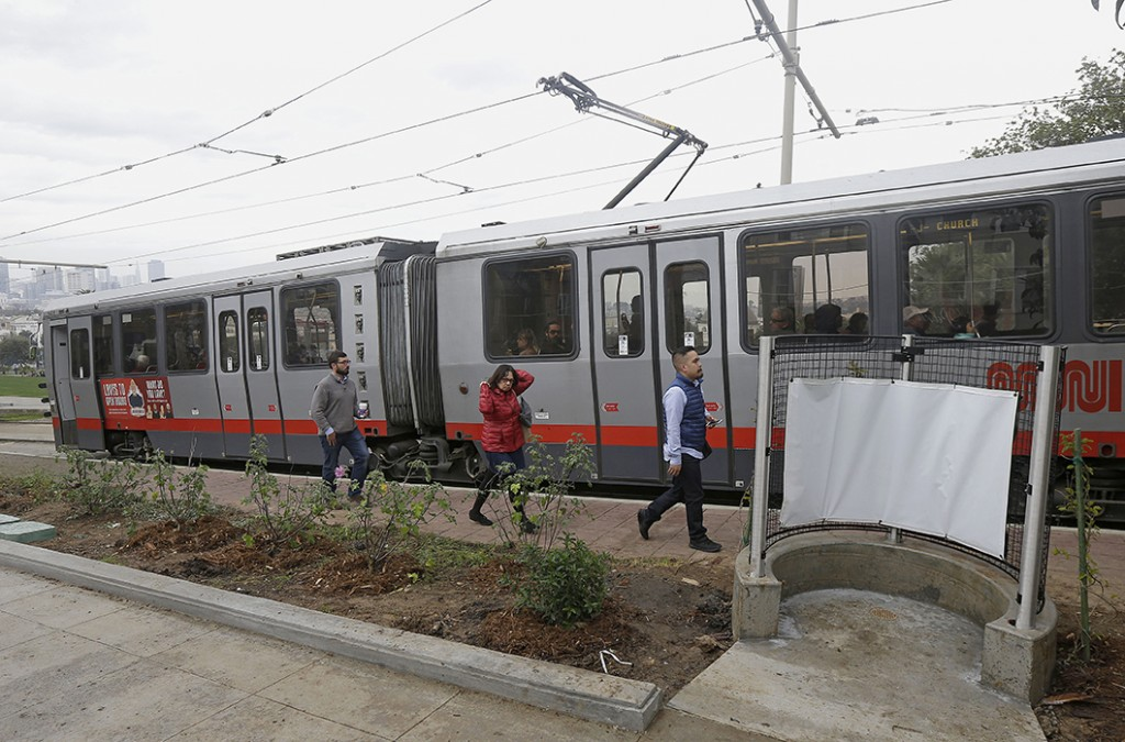 Passengers exit a San Francisco MUNI streetcar near an outdoor urinal across from Dolores Park in San Francisco. The Associated Press