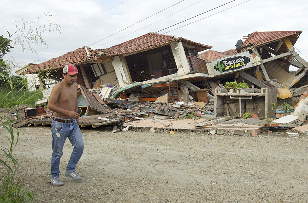 A man walks past a collapsed building in Pedernales Monday, after an earthquake struck off Ecuador's Pacific coast. The 7.8 magnitude quake is the worst the country has experienced since 1979. Reuters