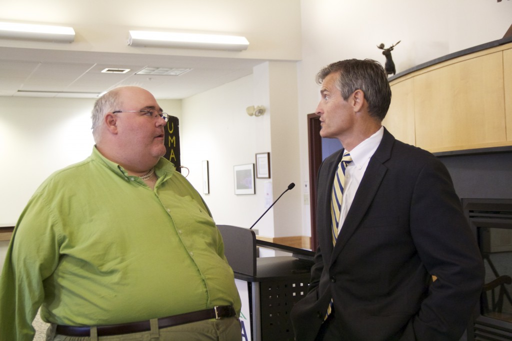 Roger Mackbach, left, speaks with former UMA President Glenn Cummings. Mackback was involved in a boating accident that ultimately ended with the loss of his right arm.