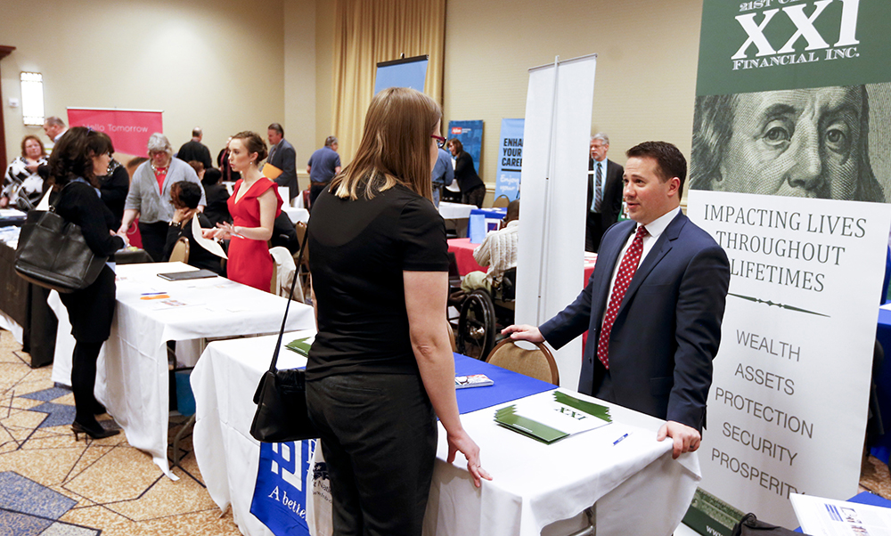 Company representatives speak with job seekers at a job fair in Pittsburgh recently. First-time claims for jobless benefits have held below 300,000 – a level typically associated with robust labor conditions – for 59 consecutive weeks. The Associated Press