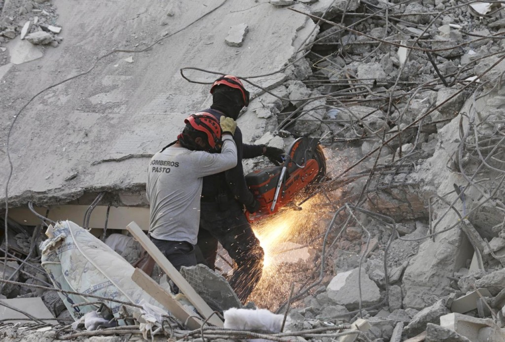 A rescue team member cuts an iron rod Tuesday at the site of a collapsed hotel in Pedernales, Ecuador. Reuters