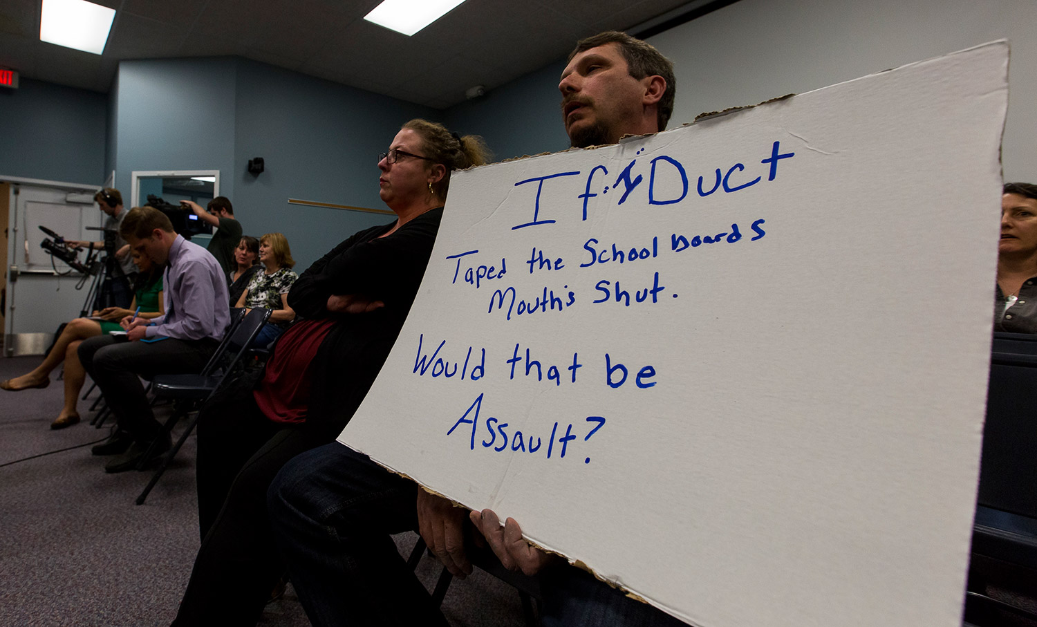 """Richard Bourgeois-Lang of Buxton holds a sign protesting the SAD 6 board's handling of the controversy surrounding Superintendent Frank Sherburne. Bourgeois-Lang and his wife, Melissa Bourgeois-Lang, left, created an outburst at the end of the meeting, after it was clear that Sherburne had not been fired. Richard Bourgeois-Lang slammed his fists on the table where the board sat, saying, """"You are not protecting our kids, you all need to go."""""""