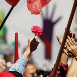 A demonstrator holds a flower during a May Day rally in support of Brazil's President Dilma Rousseff, in Sao Paulo, Brazil, on Sunday.