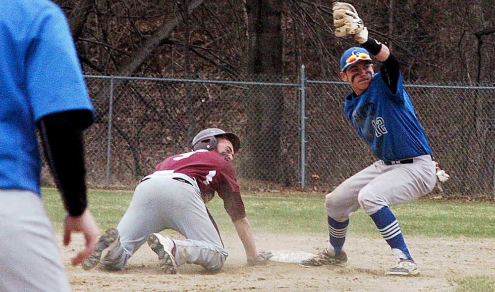University of Maine at Farmington's Jordon Croteau and Colby-Sawyer's Tim Donovan both look to the umpire for the call during game Sunday in Farmington. Croteau was called out.
