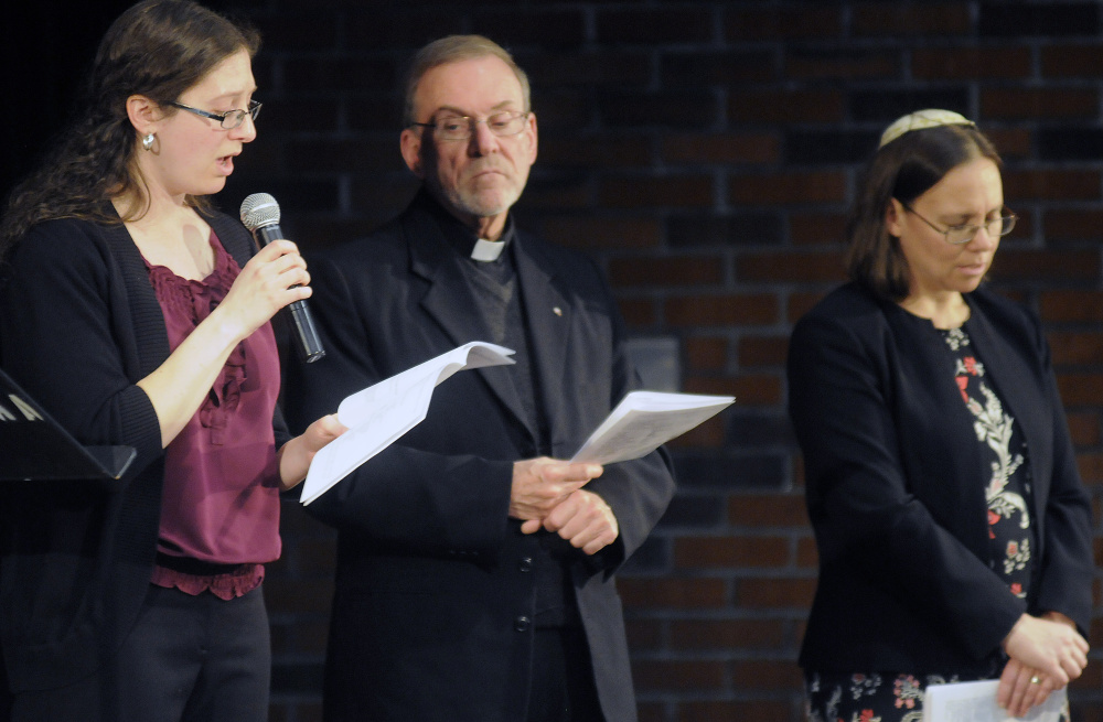 Elizabeth Helitzer sings during a service Sunday with Catholic priest Frank Morin and Rabbi Erica Asch on the Holocaust Day of Remembrance hosted by the Holocaust and Human Rights Center of Maine in Augusta.