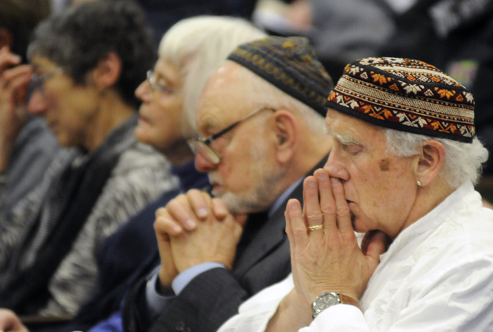 People reflect during the Holocaust Day of Remembrance hosted by the Holocaust and Human Rights Center of Maine in Augusta on Sunday.